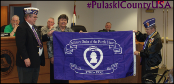 Ret SGM Edgar Izizarry and Commander Everett Kelley present the Purple Heart City flag to Waynesville Mayor, Luge Hardman. The flag will proudly be flown on special days.