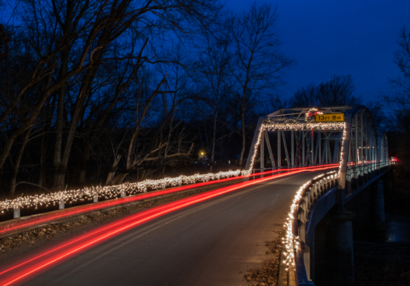 A taillight flare adds an extra zip to the festive lights on the Devils Elbow Bridge. Photo by Shawn Helgerson.